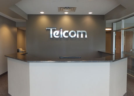 desk infront of Telcom sign